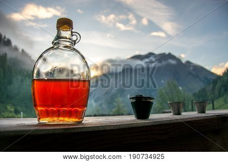 Drinking plum brandy after a long hiking tour in the mountains in Austria during sunset