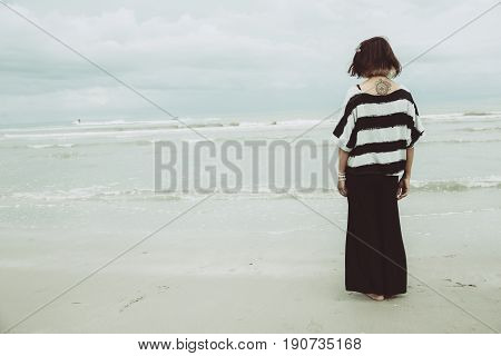portrait asian single tattoo hipster indy women lonely stand alone on the beach vintage mute color tone.