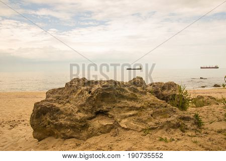 Big rock on the sunny beach with blue turquoise sea and cloudy sky and cargo ships