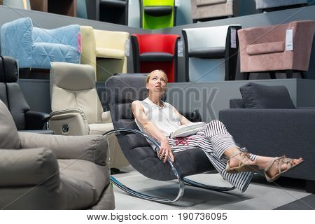 Caucasian woman shopping for furniture, recliner and home decor in store. Lady sitting on rocking chair imagining her new home architectural arrangement.
