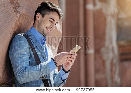 Hilarious man is holding phone and looking at screen with wide smile. He standing near vintage building. Copy space on right side