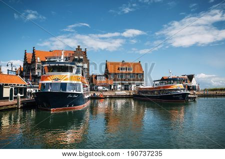 Volendam Netherlands - 26 April 2017: Harbor of Volendam with colorful tourist boats and promenade at sunny day Netherlands. Volendam is a popular tourist destination in North Holland