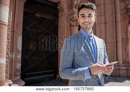 Hilarious man is standing afore solid wooden door and looking at camera with bright smile. He holding phone. Portrait. Copy space on left side
