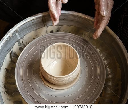 Hands of the master potter and vase of clay on the potter's wheel close-up. Master crock. Twisted potter's wheel.
