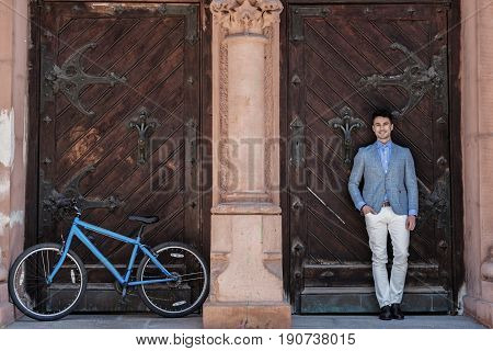 Jolly male person is leaning against wooden forged door and looking at camera with wide smile. His blue bicycle locating near neighbor entrance