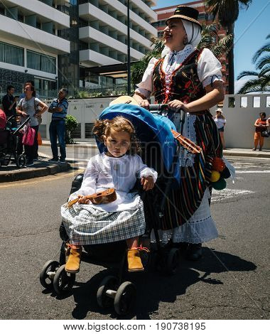 Puerto de la Cruz Tenerife Canary Islands - May 30 2017: A little girl dressed in traditional clothes sits in a stroller and holds the canary guitar Timple. Her mother in a Canarian dress. Local residents of Tenerife celebrate the Day of the Canary Island