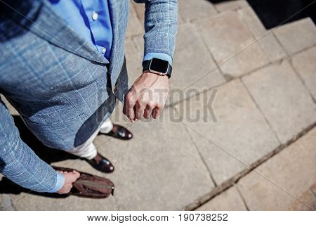 Stylish man is checking time at modern wrist watch and holding bag. Top view and cloe up of his hands. Copy space on right side