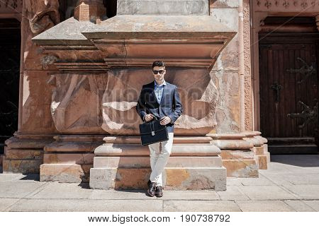 Confident man wearing sunglasses is leaning against relieve wall and holding suitcase. He attentively glancing at camera