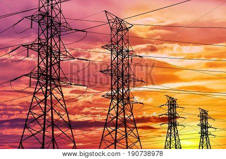 High voltage power lines and pylon towers in a bright sunset