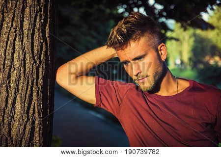 Sad, worried blond young man leaning against tree, outside in nature