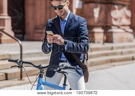 Hilarious man wearing sunglasses is stopping bike to write message at his smartphone. He sitting on bicycle. Portrait