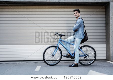 Dreamy man is getting on bike and looking up with light smile. He holding brown bag. Copy space on left side. Portrait