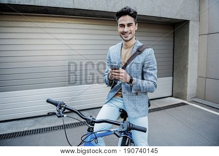 Hilarious man is sitting on bicycle and using phone. He looking at camera with bright wide smile. Portrait
