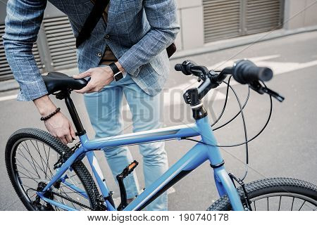 Elegant busy man is regulating seat height. He standing near bicycle. Focus on two-wheeled transport. Close up