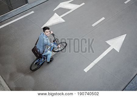 Cheerful man is riding bicycle and looking at camera with sincere smile. Top view