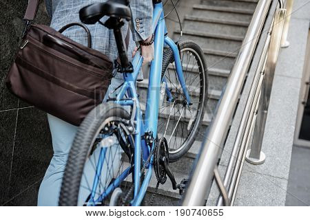 Strong man is carrying blue modern bike upstairs. Focus on two-wheeled transport