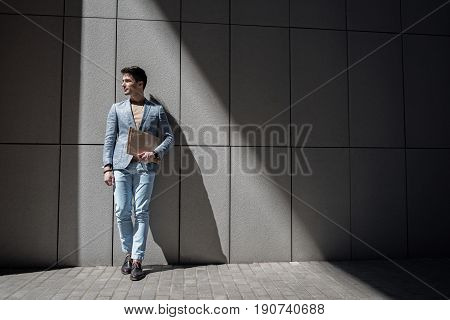 Cheerful man is leaning against wall and looking aside with wide smile. He keeping folder. Copy space on right side