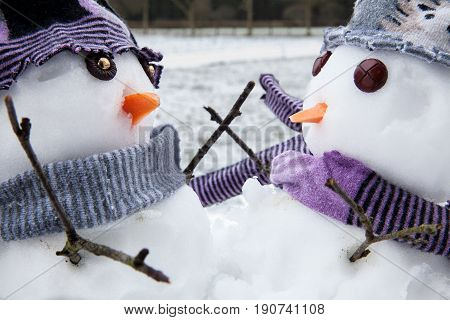 Two cute snowmen close up dressed for winter in scarfs and hats embracing each other as long lost friends. Winter scene with snow.