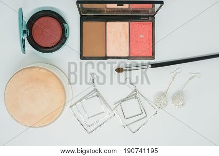 isolated cosmetics eye shadow brush and face powder and with earrings for women beauty