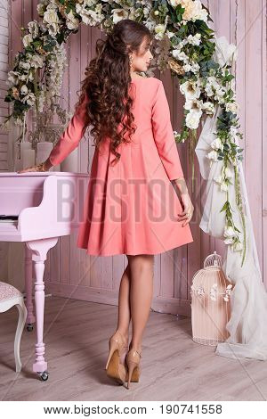 Elegant young woman in evening dress posing in interior. Fashion style portrait of a beautiful girl in interior. Women