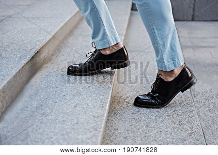 Close up of male foots wearing shiny leather oxfords. He walking up stairs outside