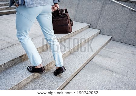 Businessman is holding brown bag and going up rungs. Close up of legs