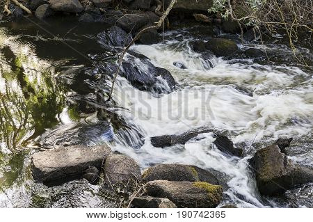Small silky waterfall in a fast river between trees