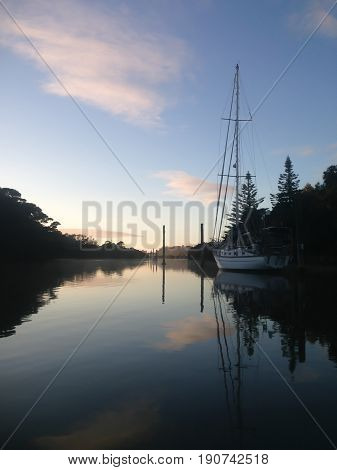 Moored yacht on Kerikeri Inlet New Zealand NZ at dawn on a winter morning with sea mist