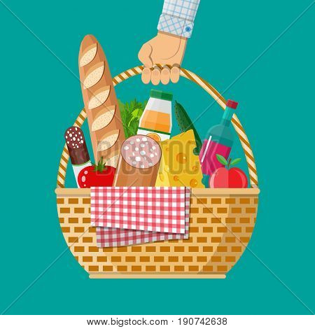 Hand holds wIcker picnic basket with gingham blanket full of products. Bottle of wine, sausage, bacon, cheese, apple, tomato, cucumber, salad, orange juice. Vector illustration in flat style