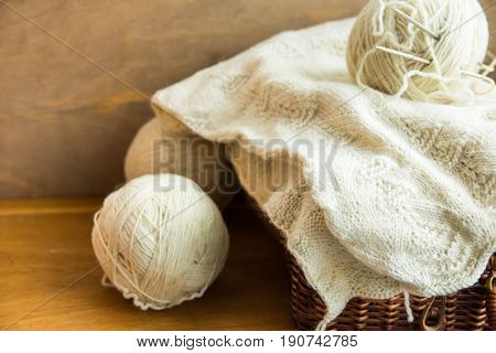 Piece of handmade knitwear clew of white wool yarn on vintage hobby and crafts wicker chest wood table cozy atmosphere shabby chic style