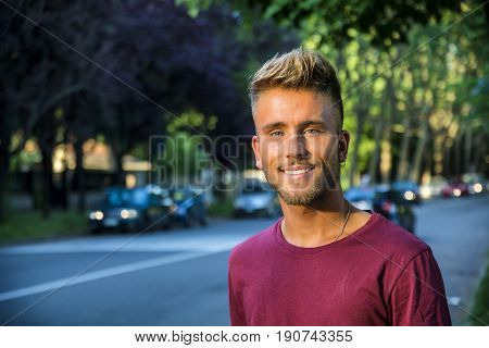 Good looking, blue eyed male model by city street, walking, looking at camera with a smile