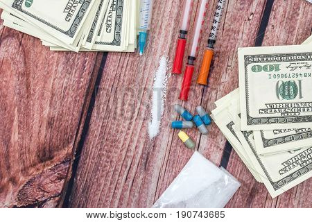 Different Pills,  Cocaine Powder,  Dollar Bills, And Syringe On Desk.
