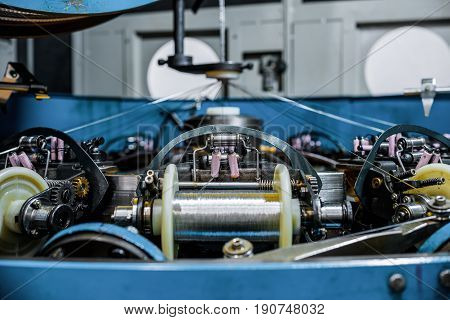 Coil with coiled wire. The mechanism of a vertical braiding machine. Abstract industrial background. Tinted image.