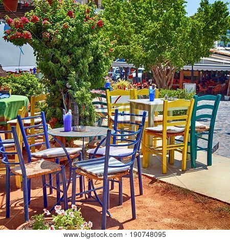 Outdoor restaurant with multicolored tables and chairs, Crete, Greece. Square image