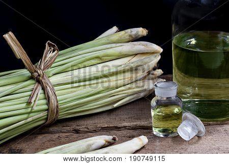 Lemon Grass (Cymbopogon citratus) and Lemongrass oil in glass bottles on wood table.