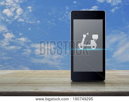 Motor bike icon on modern smart phone screen on wooden table over blue sky with white clouds Business delivery service concept