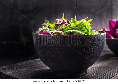 Fresh salad with arugula red chicory baked olive and parmesan cheese in a black bowl on old dark wooden board. Healthy vegan food. Selective focus free text space.