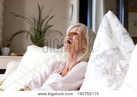 Older Woman Sitting On Sofa At Home And Laughing