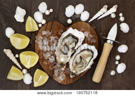 Fresh oysters on crushed ice on a heart shaped board with pearls, lemon fruit, oyster knife and shells on old oak background. High in omega 3 and protein.