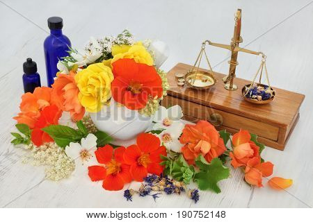 Natural flower and herb therapy with elderflower, valerian, cornflower, nasturtium, orange blossom, rose,  marjoram and ladies mantle with old brass apothecary scale and essential oil bottles.