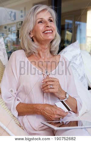 Older Woman  Witting With Bank Card And Digital Tablet
