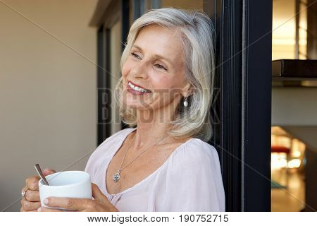 Smiling Older Woman Standing With Cup Of Coffee