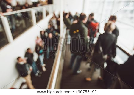 Queue at the airport for boarding. Blurred background of many people, waiting their boarding.
