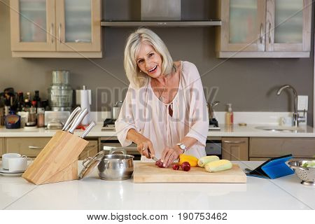 Happy Older Woman  Cutting Food On Chopping Board In Kitchen