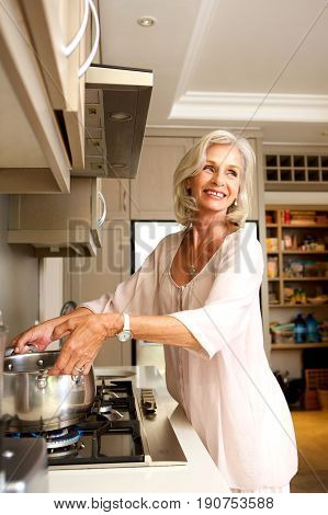 Smiling Older Woman Putting Pot On Stove