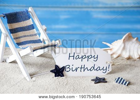 Summer Label With English Text Happy Birthday. Blue Wooden Background. Card With Holiday Greetings. Beach Vacation Symbolized By Sand, Deck Chair And Shell.
