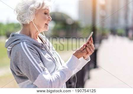 Profile of nice cheerful old woman looking with concentration at her smart phone. She is listening to music via earphones and leaning her back on city street fence