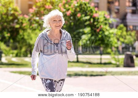 Portrait of happy senior lady jogging along city sidewalks. She is wearing active wear, smiling and looking ahead