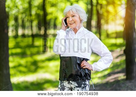 Portrait of old pretty lady standing in summer park. She is smiling and talking via mobile phone
