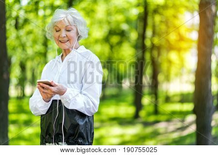 Portrait of cheerful lady communicating through her mobile phone. She is reading messages and listening to music using headphones. Copy space in right side